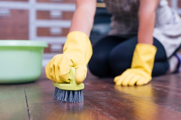 Kobieta gospodyni czyszczenia podłogi z drewna za pomocą pędzla na sobie żółte rękawiczki