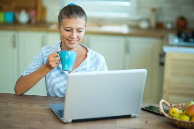 Kobieta gospodyni domowa w kuchni siedzi przy stole z laptopem. komunikuje się, relaksuje, pracuje z domu i robi zakupy online