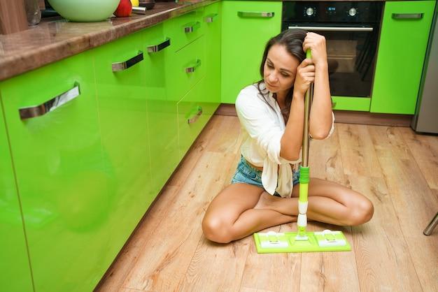 Kobieta gospodyni domowa z mopem sprzątająca podłogę w kuchni regularne sprzątanie domu kaukaska...