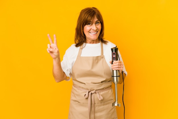 Kobieta gotować w średnim wieku trzyma mikser na białym tle pokazuje numer dwa palcami