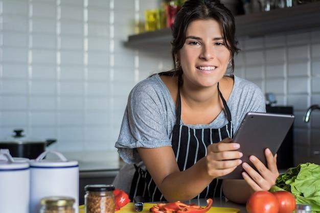 Kobieta gotowania i przestrzeganie przepisu na komputerze typu tablet