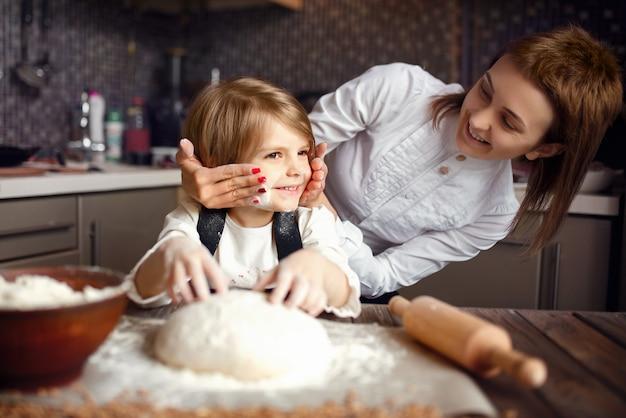 Kobieta gotowania i zabawy z małą dziewczynką