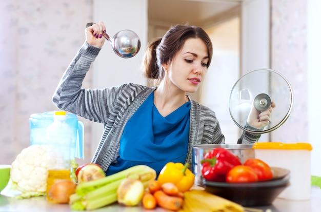 Kobieta gotowania veggie lunch z laddle