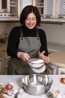 Kobieta gotowania w fartuchu przesiewa mąkę w metalowej misce