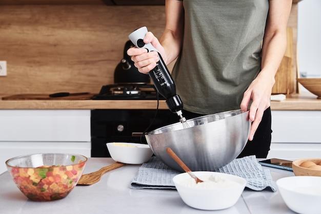 Kobieta gotowanie ciasta w kuchni. ręce ubij ciasto mikserem elektrycznym