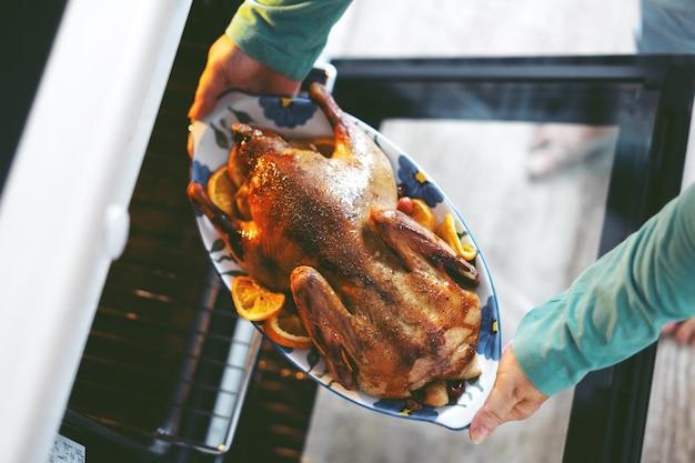 Kobieta gotowanie kaczki z warzywami i wkładanie jej z piekarnika.