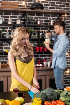 Kobieta gotowanie. szczupła, atrakcyjna kobieta z blond falującymi włosami gotuje sałatkę w kuchni ze swoim kochającym mężem
