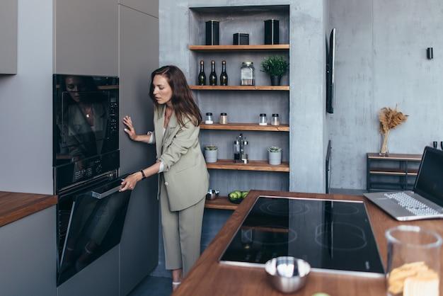 Kobieta gotuje jedzenie w piekarniku i sprawdza, czy jest gotowe.