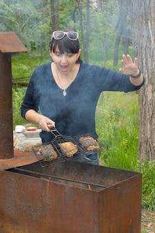 Kobieta gotuje na grillu