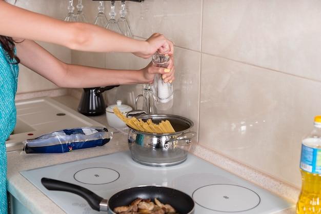 Kobieta gotuje spaghetti w rondlu ze stali nierdzewnej na płycie grzejnej na kuchence, dodając sól z młynka, aby przyprawić makaron
