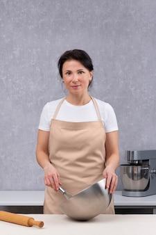 Kobieta gotuje w kuchni i trzyma w rękach metalową miskę. rama pionowa.