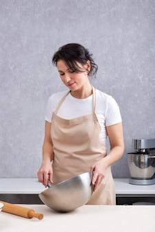 Kobieta gotuje w kuchni z miską w dłoniach. rama pionowa.