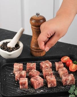 Kobieta gotuje z solą świeże surowe steki saikoro pokrojone w kostkę z marmurkowej japońskiej wołowiny na białym tle kuchni.