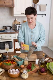 Kobieta gotuje zdrowe jedzenie w domu at