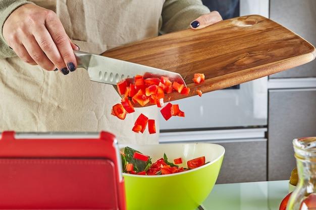 Kobieta gotuje zgodnie z samouczkiem wirtualnej klasy mistrzowskiej online i patrząc na cyfrowy przepis, używając tabletu z ekranem dotykowym podczas gotowania zdrowego posiłku w kuchni w domu.