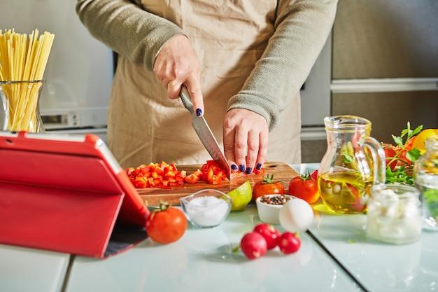 Kobieta gotuje zgodnie z samouczkiem wirtualnej klasy mistrzowskiej online i patrzy na cyfrowy przepis, używając tabletu z ekranem dotykowym podczas gotowania zdrowego posiłku