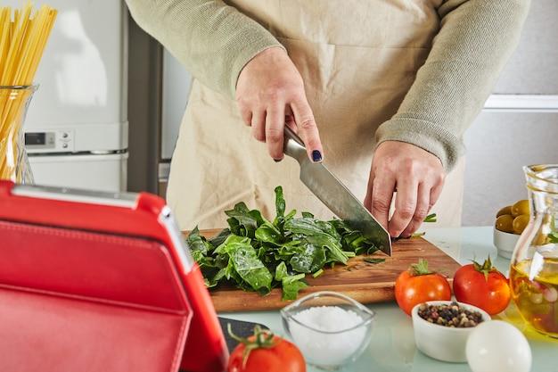 Kobieta gotuje zgodnie z samouczkiem wirtualnej klasy mistrzowskiej online