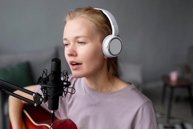 Kobieta gra na gitarze i śpiewa