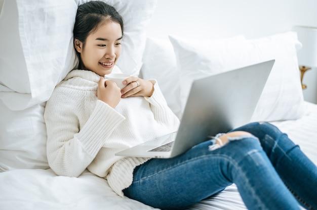 Kobieta gra na laptopie i trzyma filiżankę kawy.