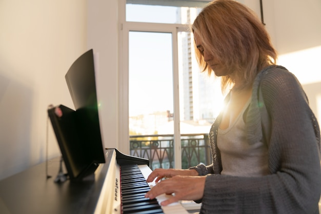 Kobieta gra na pianinie elektronicznym na tle dużego okna, przez które wpada przez okno jasne światło słoneczne