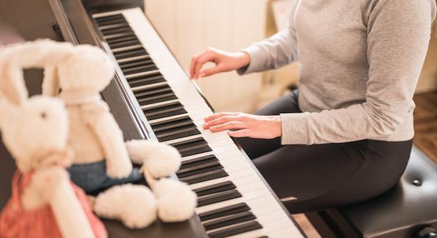 Kobieta gra na pianinie z wypchanymi zwierzętami królikami