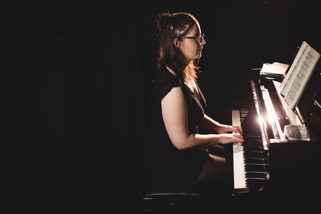 Kobieta gra na pianinie