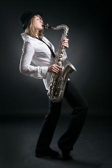 Kobieta gra na saksofonie na czarnym tle