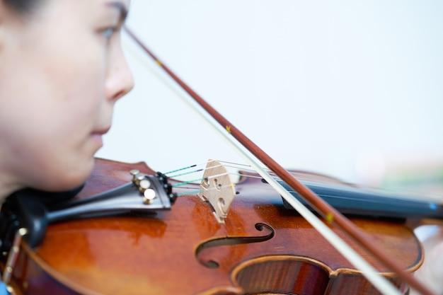 Kobieta gra na skrzypcach cięciwą