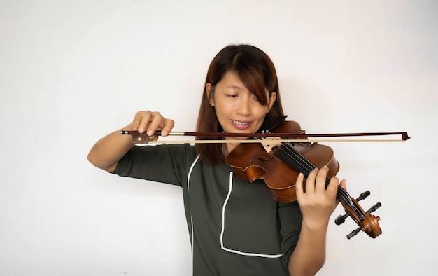 Kobieta gra na skrzypcach na białym tle w kolorze białym