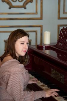 Kobieta gra na starym pianinie. brunetka o europejskim wyglądzie