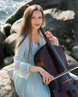 Kobieta gra na wiolonczeli nad morzem ze skałami