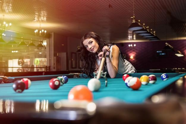 Kobieta gra w bilard i używa stojaka na most