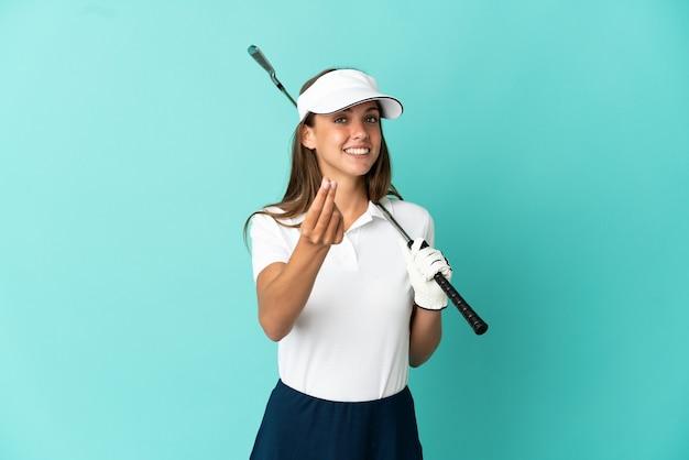 Kobieta gra w golfa na odosobnionym niebieskim tle dokonywania gestów pieniędzy