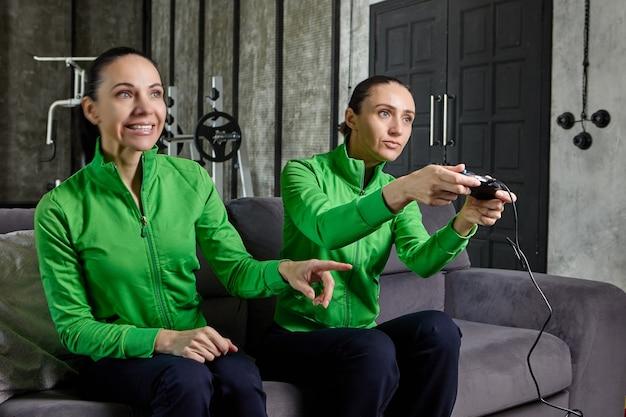 Kobieta gra w grę komputerową pod okiem siostry