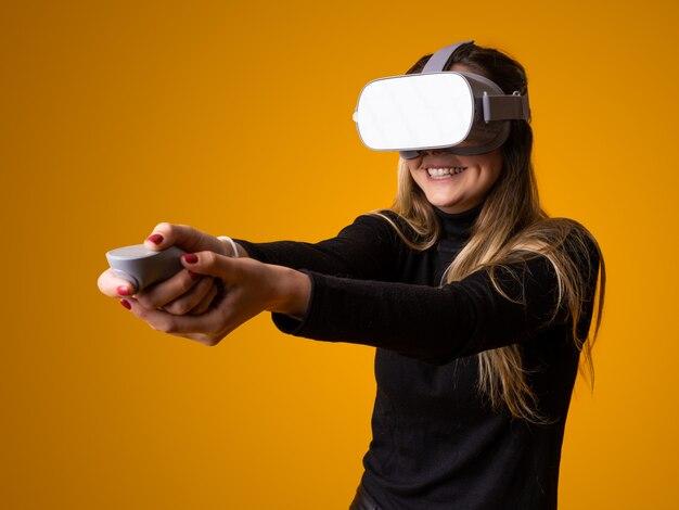 Kobieta gra w grę wideo za pomocą urządzenia wirtualnej rzeczywistości