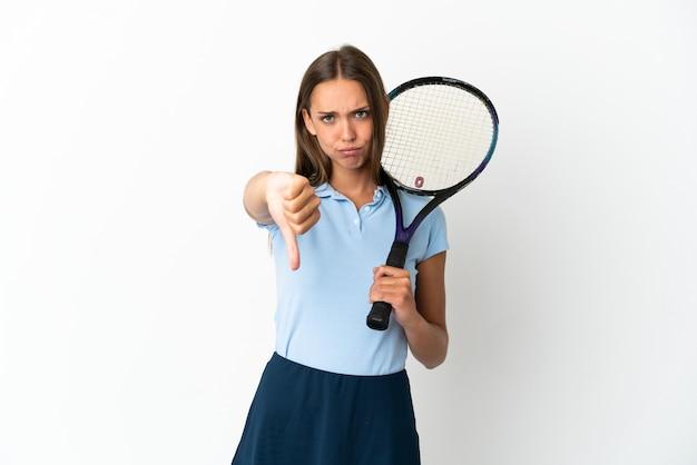 Kobieta gra w tenisa na odosobnionej białej ścianie pokazując kciuk w dół z negatywnym wyrazem twarzy