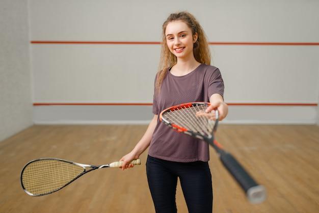 Kobieta gracz daje rakietę do squasha. dziewczyna na treningu gry, aktywne hobby sportowe na korcie, sprawny trening dla zdrowego stylu życia