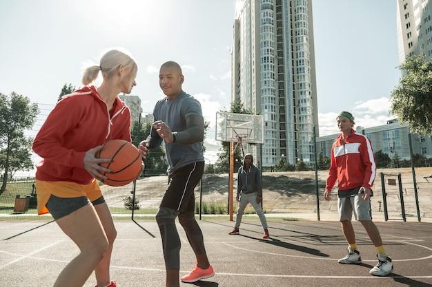 Kobieta gracz. miła młoda kobieta trzyma piłkę podczas biegania z nim podczas meczu
