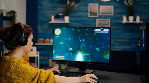 Kobieta gracz oddanie słuchawek grając w kosmiczną grę online na profesjonalnym komputerze w domu późną nocą. gracz testujący kosmiczną strzelankę online z nowoczesną grafiką, stylowym pokojem do gier kosmicznych