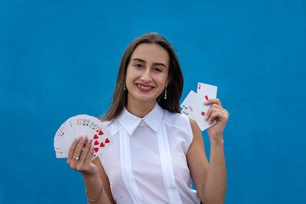 Kobieta gracz posiadający karty pokera na białym tle na niebieskim tle. gra