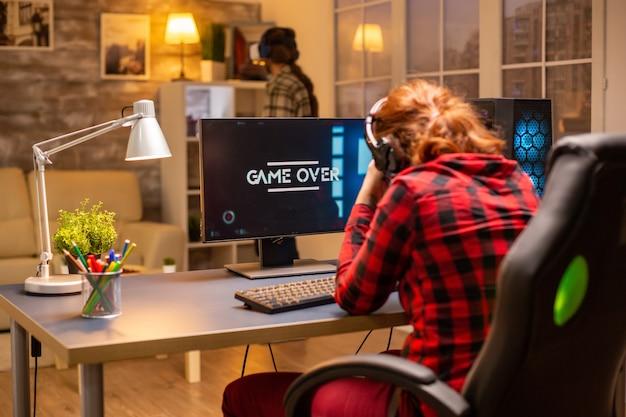 Kobieta-gracz przegrywająca grę wideo grającą późno w nocy w salonie.