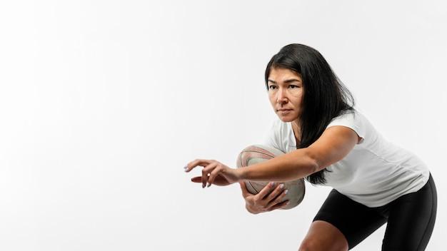 Kobieta gracz rugby trzymając piłkę z miejsca na kopię