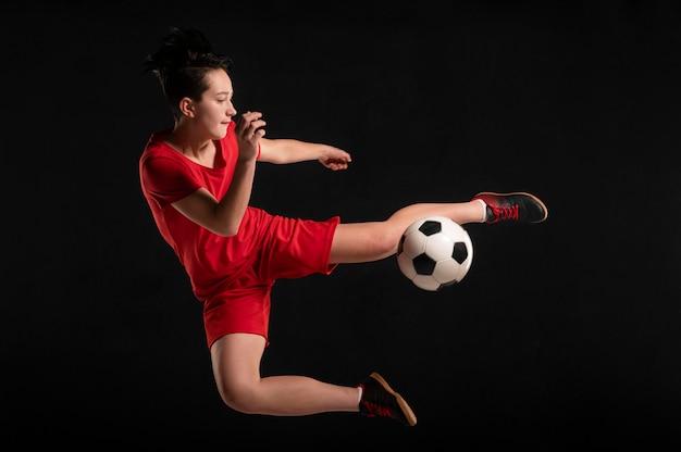 Kobieta gracz skacze i kopie piłkę