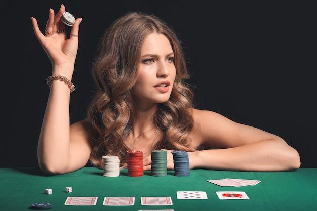 Kobieta gracz w pokera przy stole w kasynie