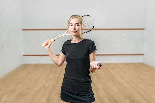 Kobieta gracz w squasha z rakietą i piłką w rękach