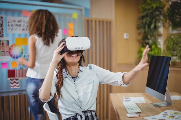 Kobieta grafik korzystający z zestawu słuchawkowego wirtualnej rzeczywistości z kolegą w tle