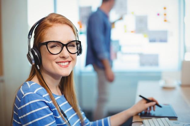Kobieta grafik pracujący ze słuchawkami