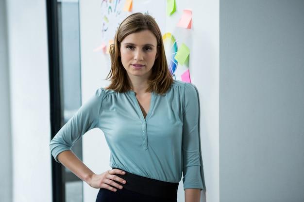 Kobieta grafik stojący z ręką na biodrze w kreatywnym biurze