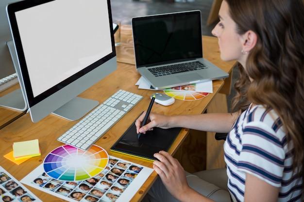Kobieta grafik za pomocą tabletu graficznego przy biurku