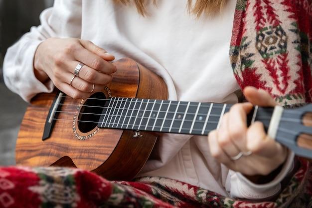 Kobieta grająca na hawajskiej gitarze, śpiewa piosenkę na vintage ukulele w domu. selektywne ustawianie ostrości